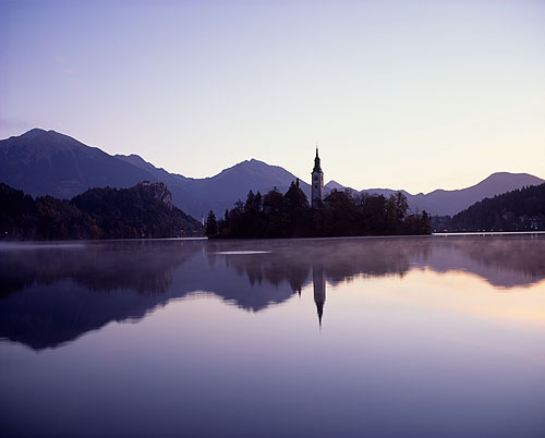 Lake Bled and the island Otok with the Church of the Assumption with Bled Castle behind at dawn.